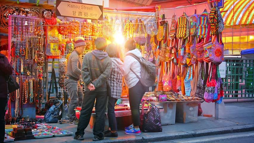 HONG KONG. CHINA - CIRCA JAN 2015: Customers browsing a vendor's wares at a stall at the Jade Market on Kansu Street in busy. downtown Hong Kong.