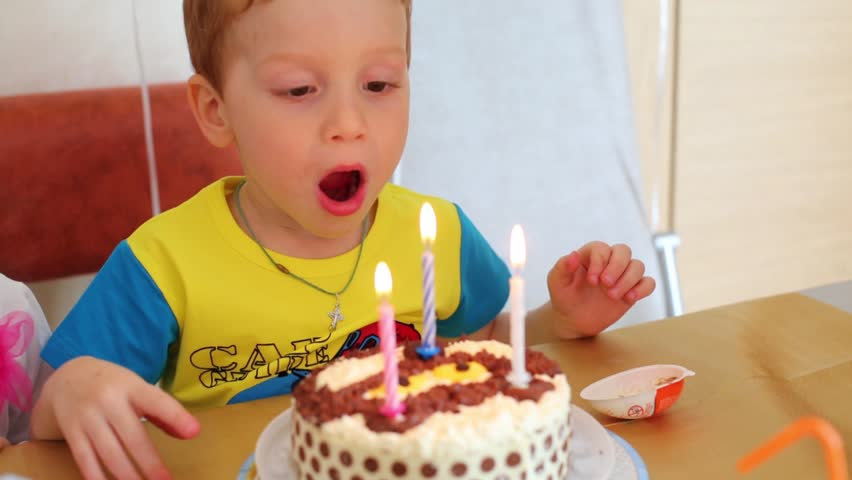 Happy boy blows out three candles on birthday cake - HD stock footage clip