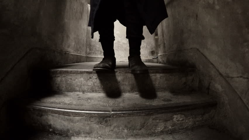 Mysterious feet walking down concrete steps. A stranger in boots descends a dark shadowy, dirty set of stairs in an industrial type of area. Stalker or killer following his victim.