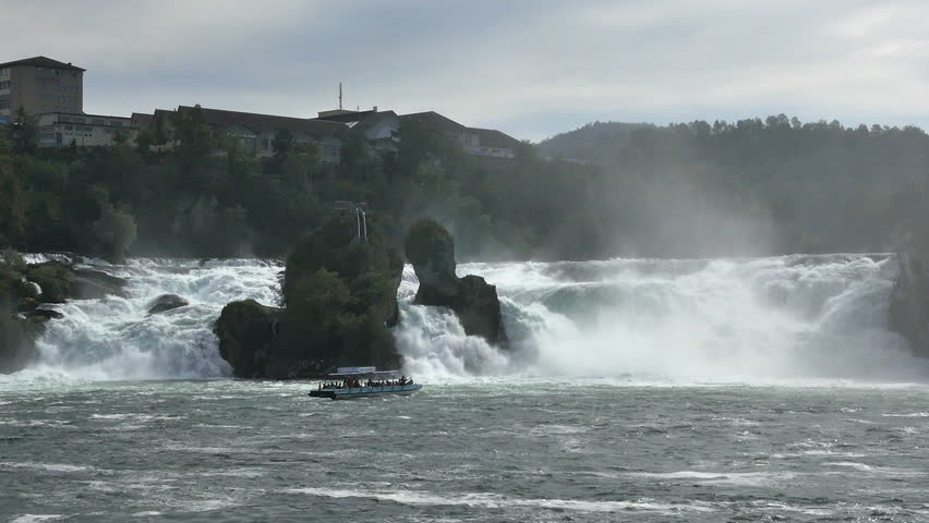 RHINE FALLS, SWITZERLAND - SEPT. 2014: Tour-boat takes tourists close to Rhine Falls  near the town of Schaffhausen,Switzerland. Tour-boats take tourists up to the mists below the falls.  - HD stock video clip