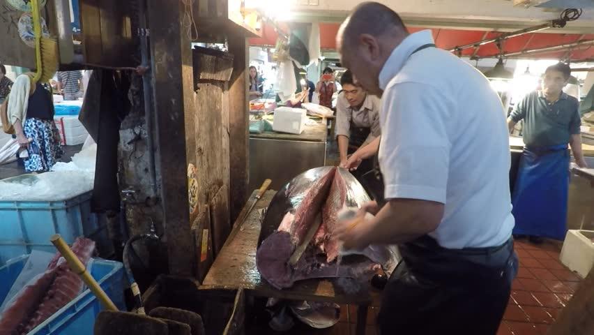 Tokyo, Japan - May 14, 2015: Fresh Tuna main cut by professional Japanese tuna handler at famous Tsukiji fish and seafood market, right after the Tuna auction. - 4K stock footage clip