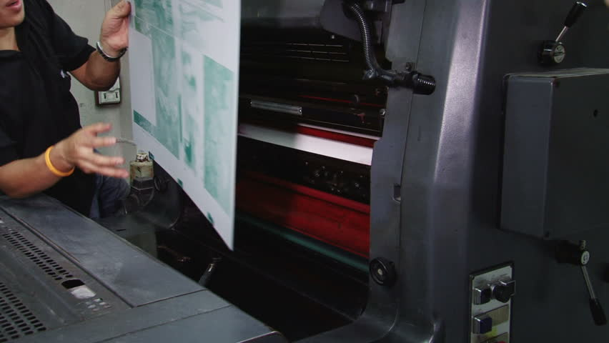 Printer fixing a plate onto the print machine cylinder. All images in the clip are property released. - HD stock video clip