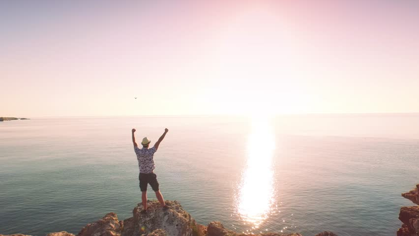 Successful Young Man Silhouette Standing On Ocean Cliff Aerial Raising Arms Happiness Joy Freedom Concept  - 4K stock footage clip
