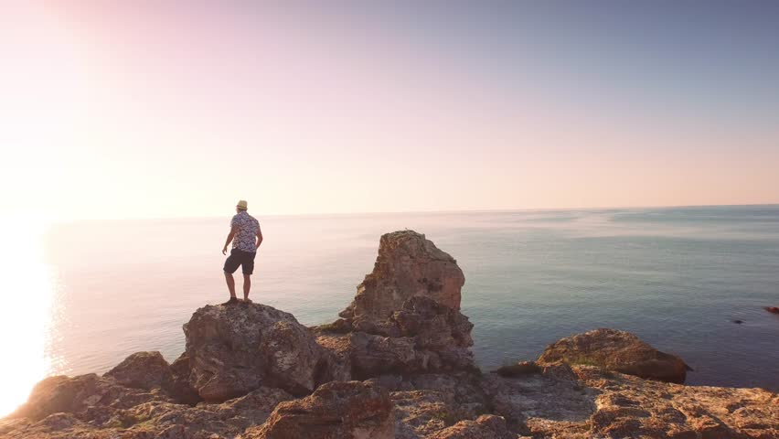 Aerial Of Young Handsome Businessman Silhouette Walking Standing On Ocean Cliff Edge Sea Vacation Happiness Concept - 4K stock video clip