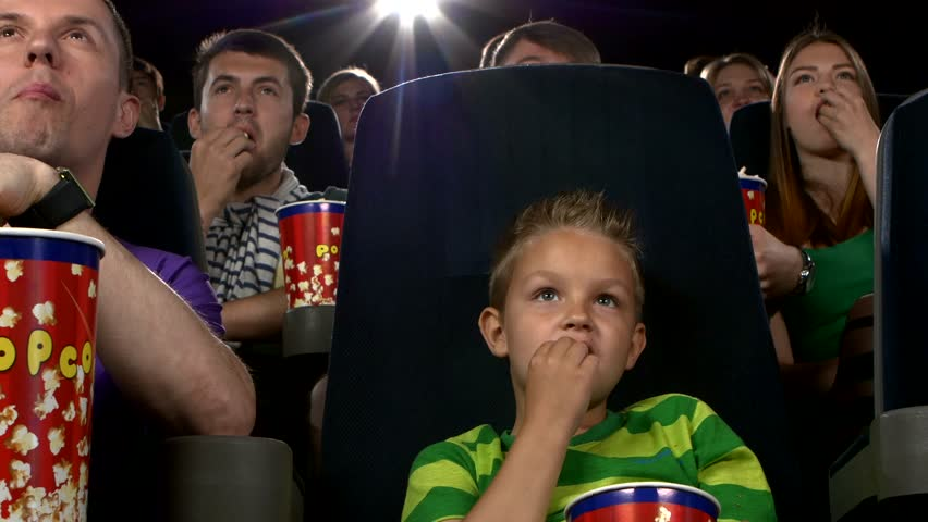 Little Boy Eating Popcorn And Watching A Movie At The ...