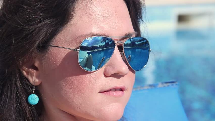 Pretty woman puts sunscreen oil on body, sunglasses reflection