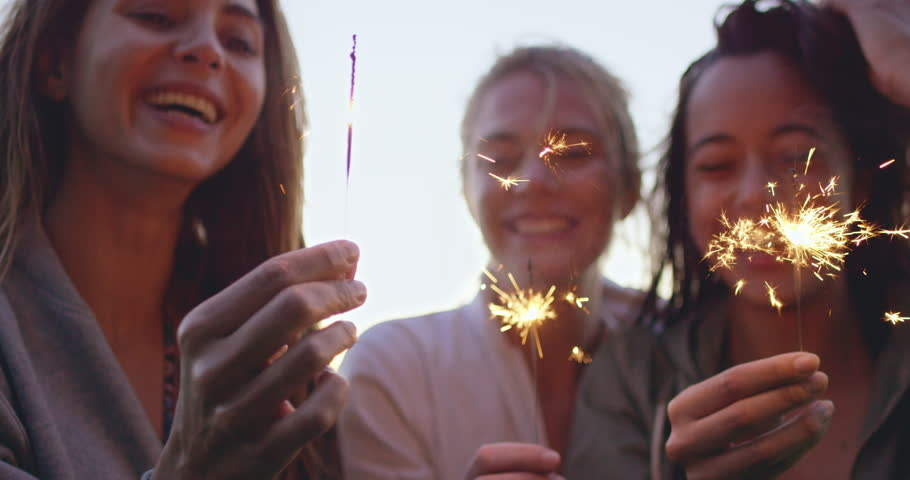 close up shot of teenage girls with sparklers celebrate and laugh
