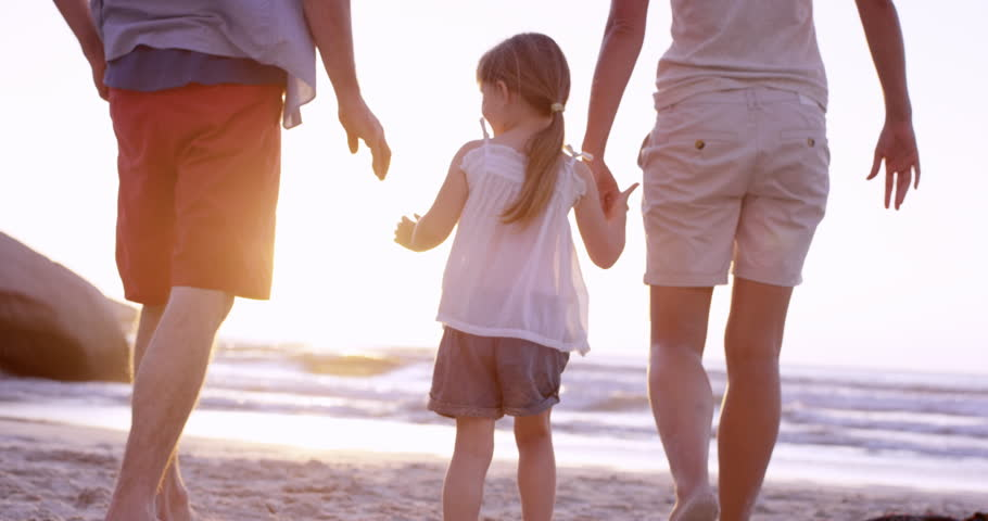 Happy family on the beach holding hands swinging little girl around at sunset on vacation slow motion RED DRAGON - 4K stock footage clip