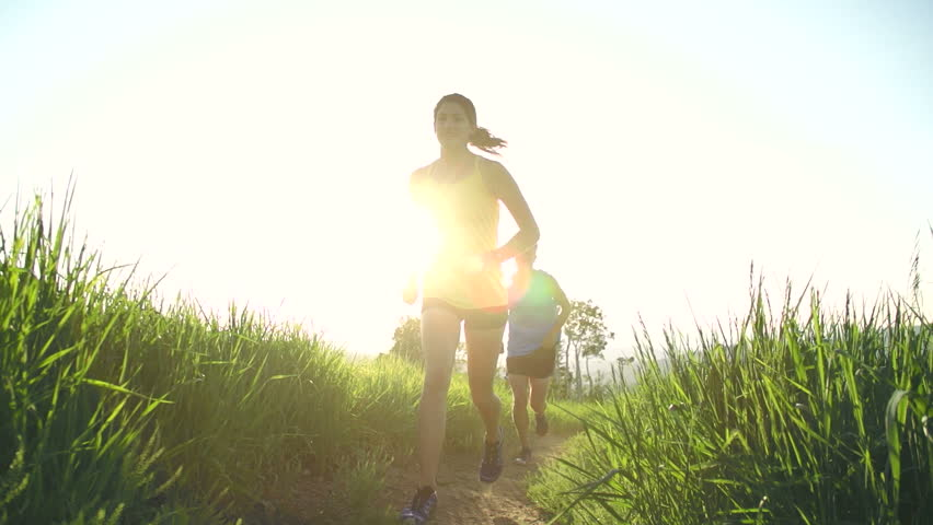 Couple Running At Grassy Park During Sunset