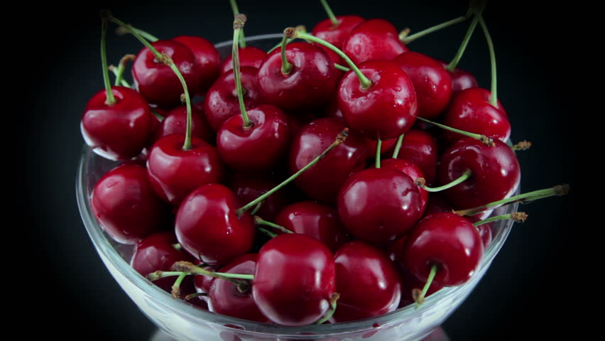 A Group of Ripe Red Cherries in a Beautiful Plate, Rotating on The Table.