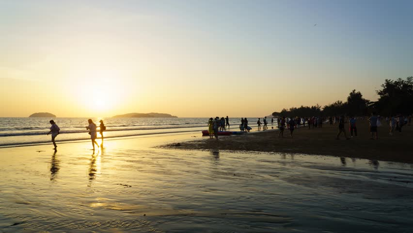 Time lapse of setting sun sunset with crowd silhouettes at the famous Tanjung Aru Beach Sabah Malaysian Borneo.