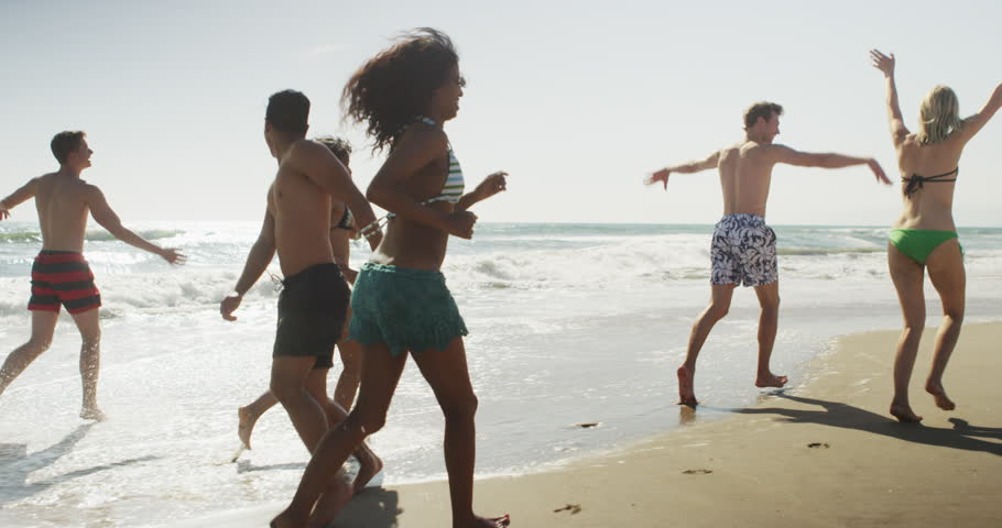 Healthy Group of multi ethnic friends running along beach shore jumping