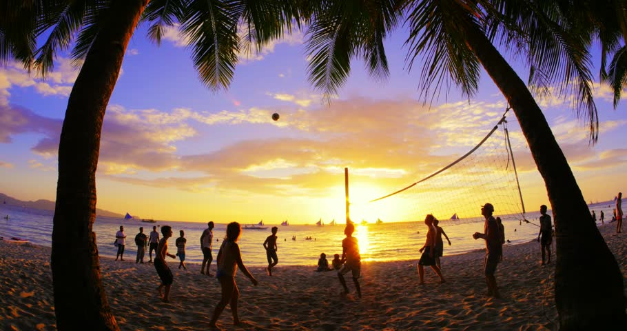BORACAY, PHILIPPINES 9 FEB 2015: Unidentified volleyball players enjoy warm sunset time and play ball on tropical sandy beach. Lifestyle activity background