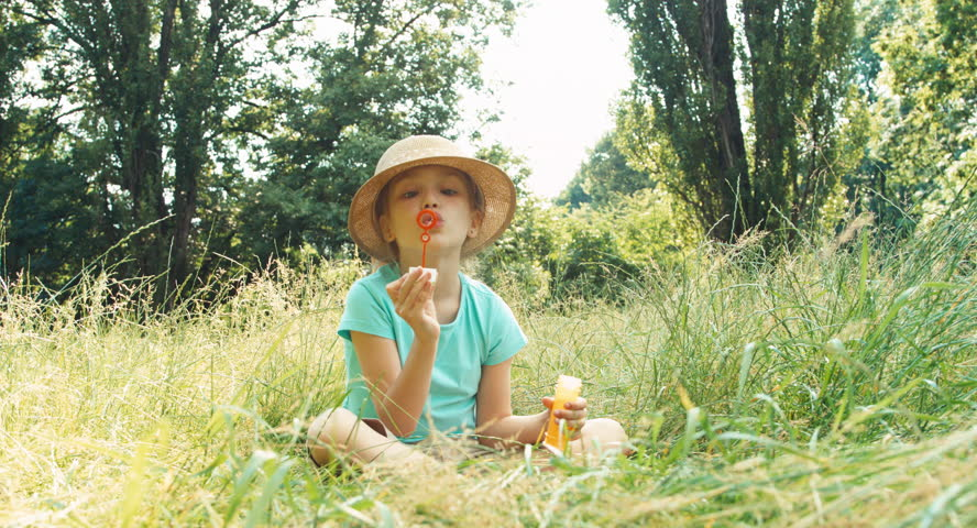 Laughing girl playing with soap bubbles in the grass and smiling at camera - 4K stock footage clip