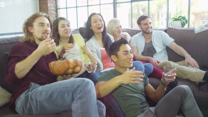 Group of attractive friends sit and eat popcorn whilst watching television.