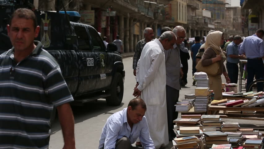 BAGHDAD, IRAQ - MAY 2015: Men looking for books at Mutanabbi Street, Police patrol in background. Mutanabbi Street where writers and intellectuals meet is the historic center of Baghdad bookselling