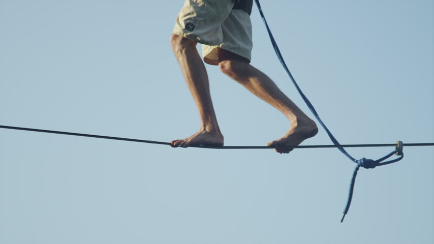 CLOSE UP of the mans feet walking on the slackline