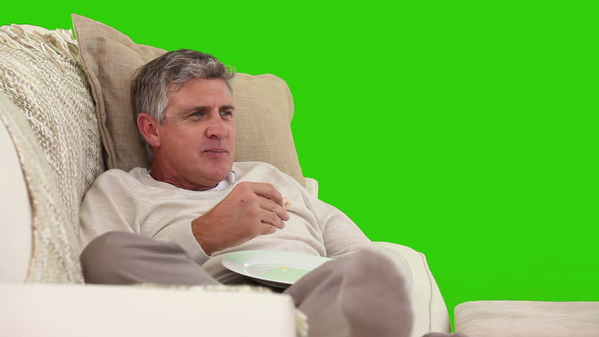 Chroma-key footage of a retired man eating a sandwich in front of the tv - HD stock footage clip