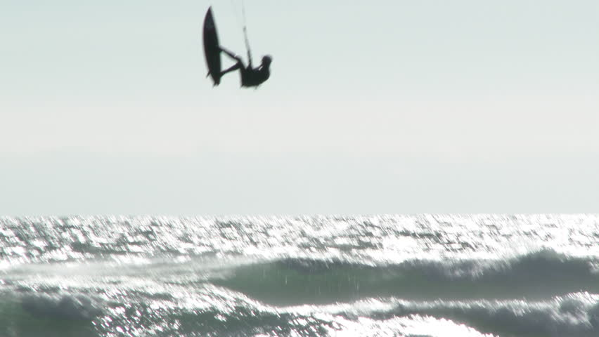 Unrecognizable person kite surfing the Pacific Ocean at the Oregon Coast hits wave for some serious, big air.