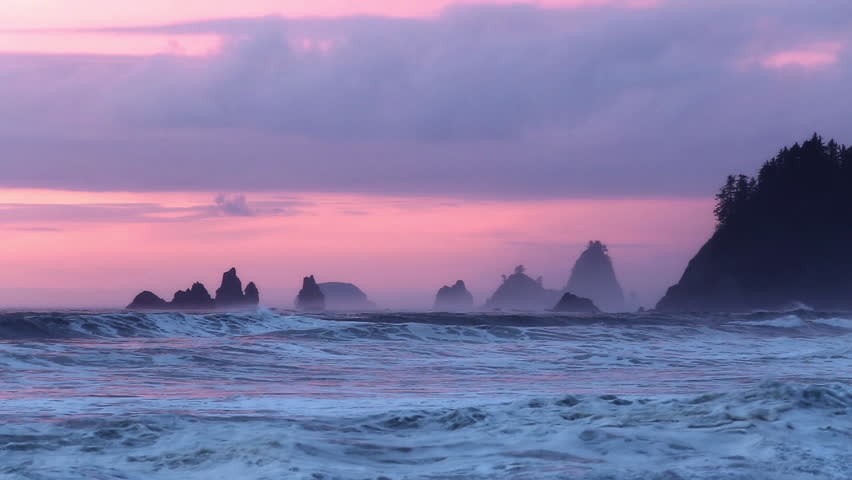 Waves breaking at sunset time with rock stack formations along the pacific coast