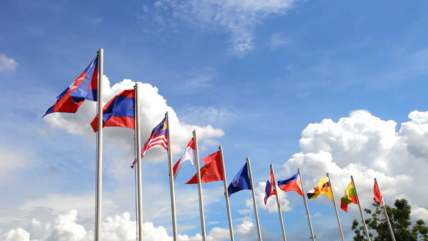 AEC or ASEAN flag waving atop among Southeast Asia nation flags on blue sky backgrund - HD stock footage clip