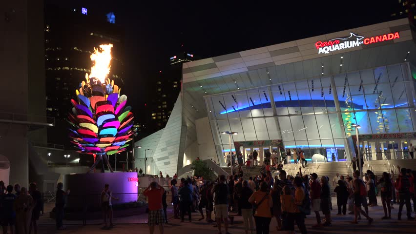 TORONTO,CANADA-JULY 18, 2015: The Pan Am or Pan American flame by the CN Tower and Ripley Aquarium has become a city's attraction. It was lit on the Games Opening Ceremony by Steve Nash