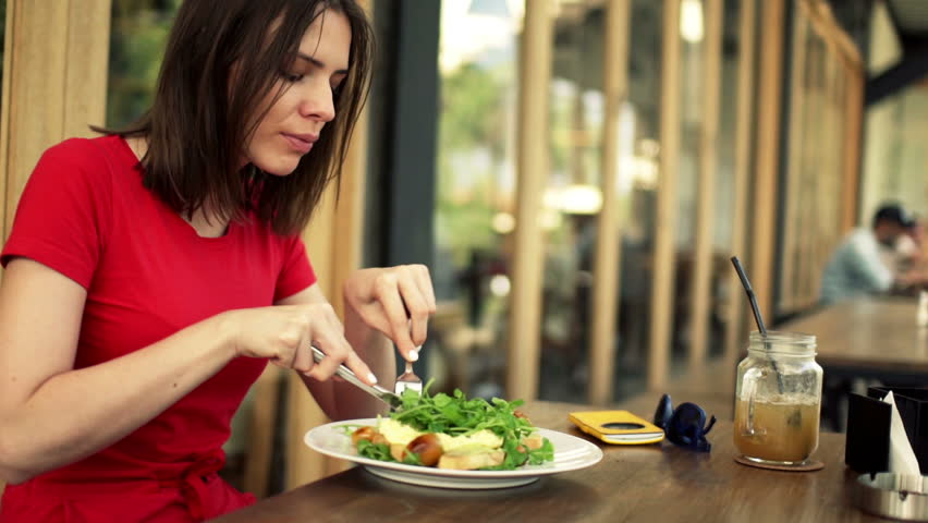 Young, pretty woman eating salad in cafe