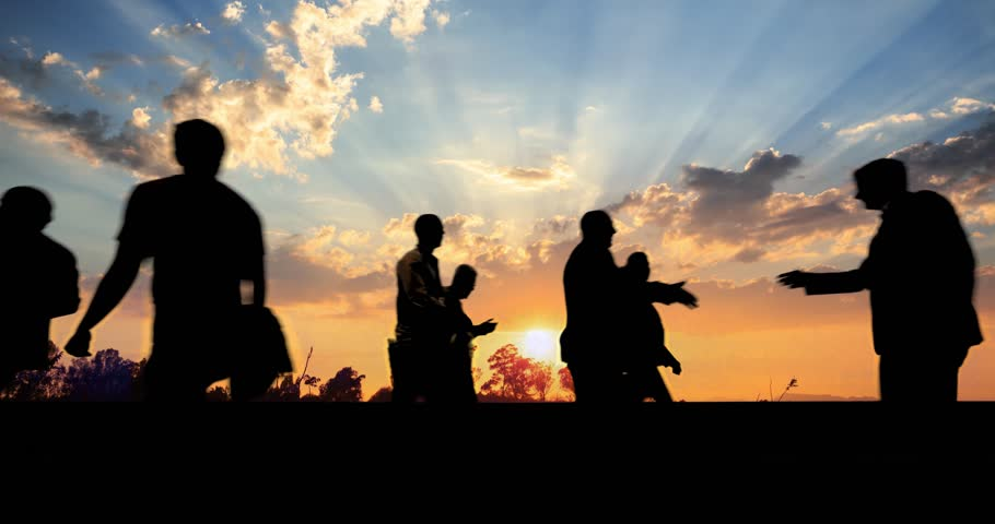 Group of business people silhouettes walking against beautiful sunset sky background. 4K UHD.