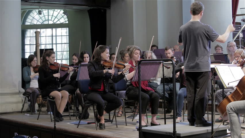 LONDON, UK - 8 JUNE 2013: Candid video footage and a slow pan across a violin section of a classical symphony orchestra to settle on the front desk strings during rehearsal.