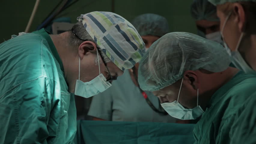 Surgeons close up. Surgical team performing operation in the operating room. Surgery on specialized clinic. Patient lying on the operating table. Surgeons operate patient in hospital theater. Close up
