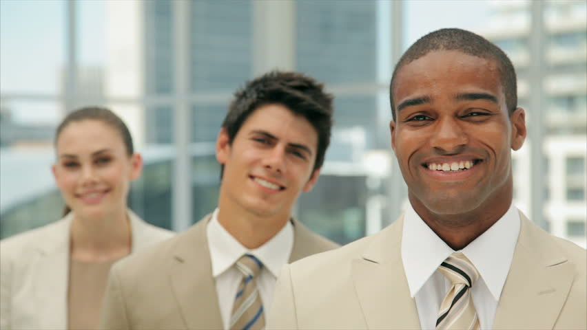 Tilt up shot of young businessman with colleagues smiling. Young business people are in formals. Multi-ethnic male and female professionals are in brightly lit office.