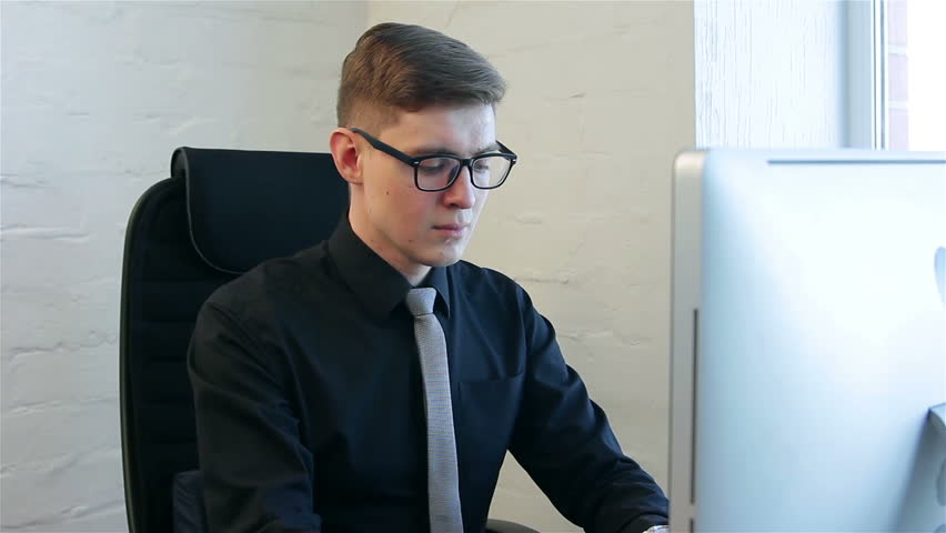Young man at work in a office. Businessman receives a phone call