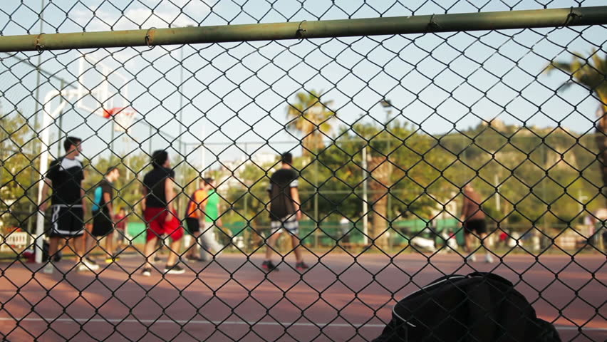 Young men play streetball (out of focus, focus on foreground). Basketball game background. Dolly shot.