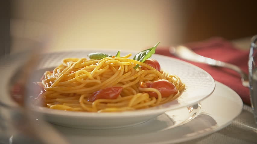 Parmesan cheese  falling in slow motion on a dish of spaghetti with tomato sauce