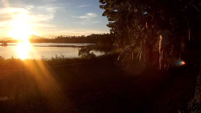 LAGUNA, PHILIPPINES - AUGUST 2, 2015: Cyclists and joggers choose lakeshore as their exercise venue. Silhouettes