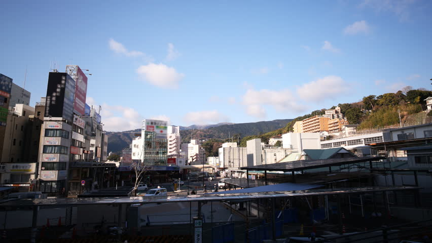Time lapse footage with tilt up motion of cloudscape over Atami Station in Shizuoka, Japan