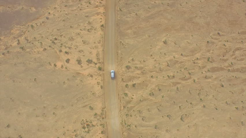 AERIAL: Flying above the car driving through huge sandy desert above the spectacular ocean cliff