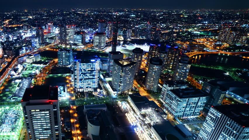 Time lapse footage with pan left motion of metropolitan cityscape at night shot from Yokohama Landmark Tower in Japan