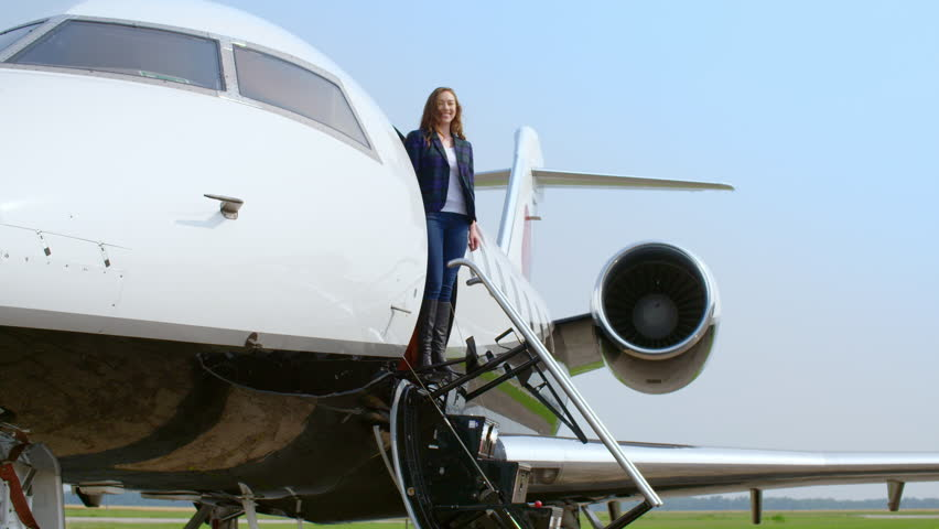 Attractive brunette in a blue jacket and jeans steps out on to the stairs of a private business jet, then smiles.  Wide view, originally recorded in slow motion 4K at 60fps.