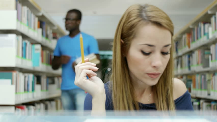 Caucasian female college student reading book in library, with african american man taking book from shelves in background. Dolly shot - HD stock video clip