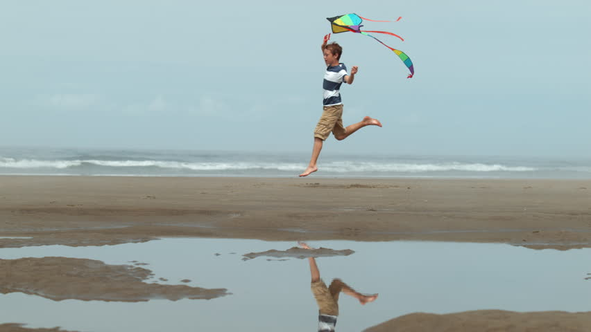 Boy running with kite at beach, slow motion