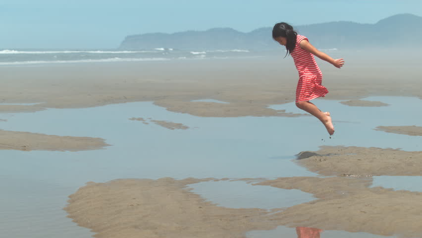 Girl jumping into puddle at beach, slow motion