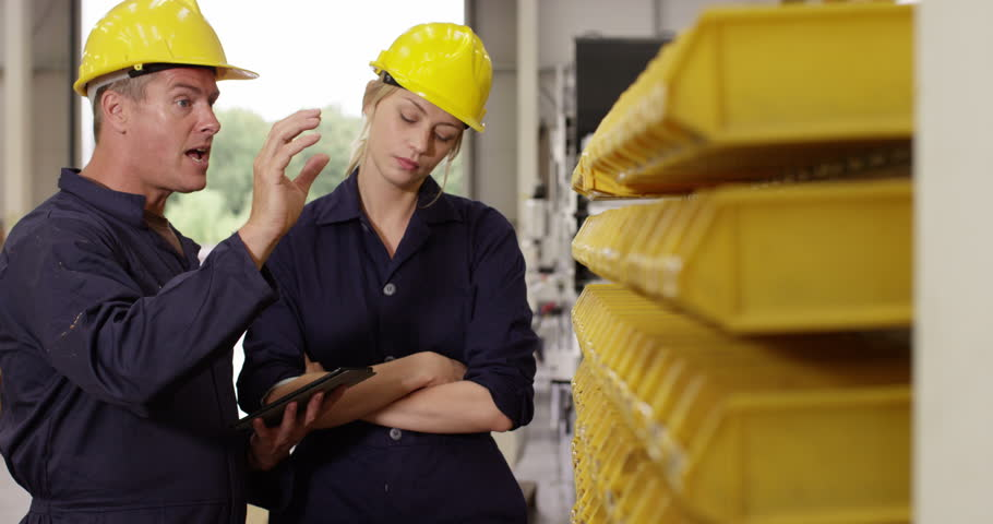 Portrait of two managers looking at stock in a large warehouse