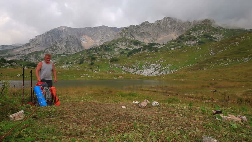 Male tourist sets campt tent in the mountains