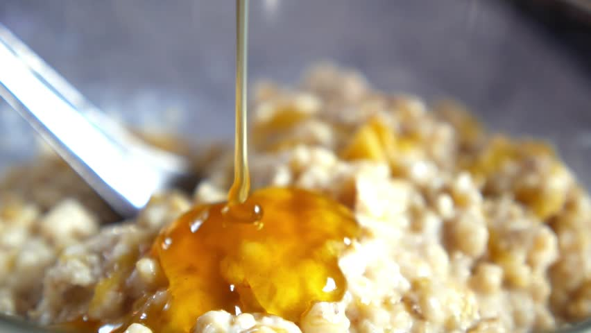 Healthy Breakfast - Oatmeal with Pouring Honey Close-up. HD, 1920x1080.