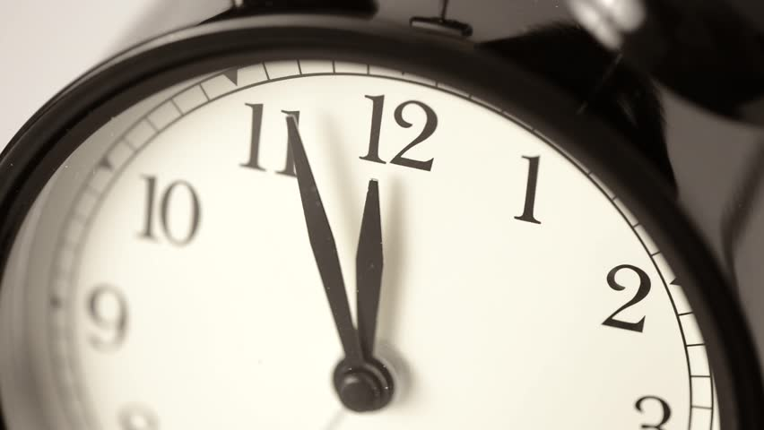 Alarm clock almost at 12 o'clock. Conceptual footage of deadline, urgency and time running out.