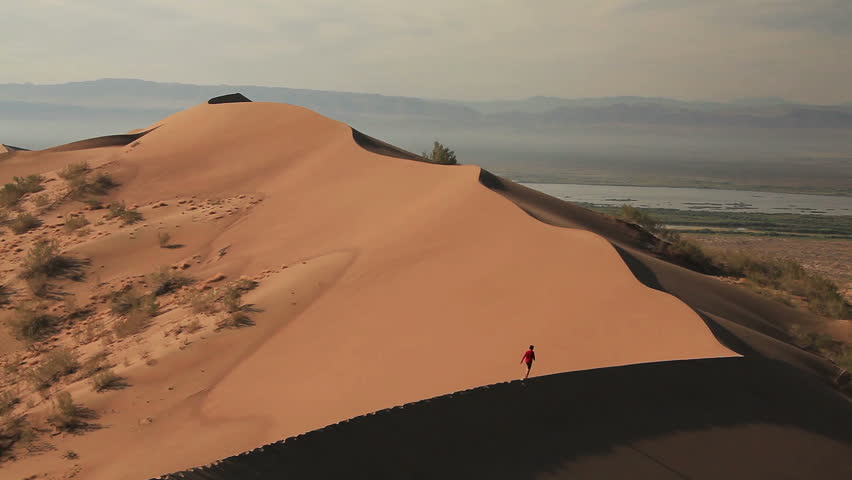 Unrecognizable man ascent on the sand dune in the desert. Canon 5D Mk II.