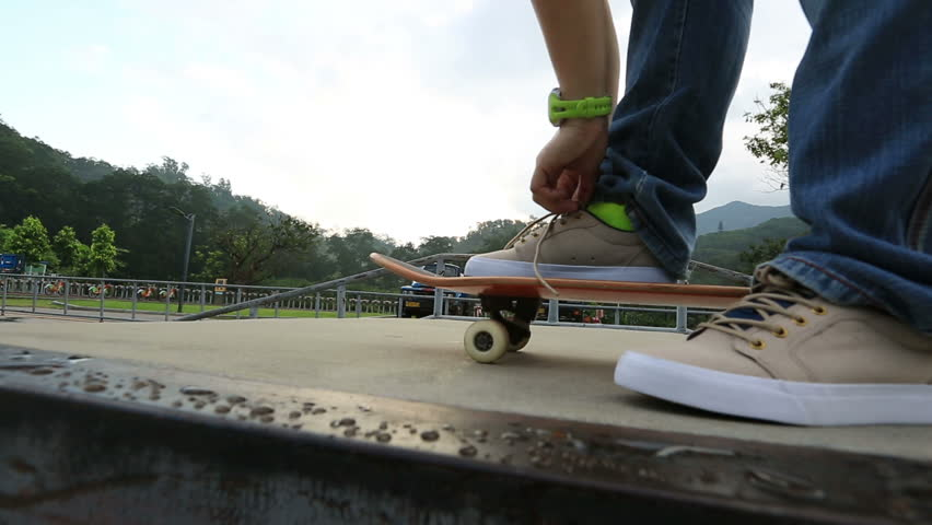 skateboarder tying shoelace at skatepark