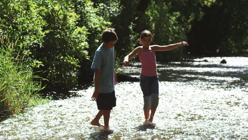 children wading in a river