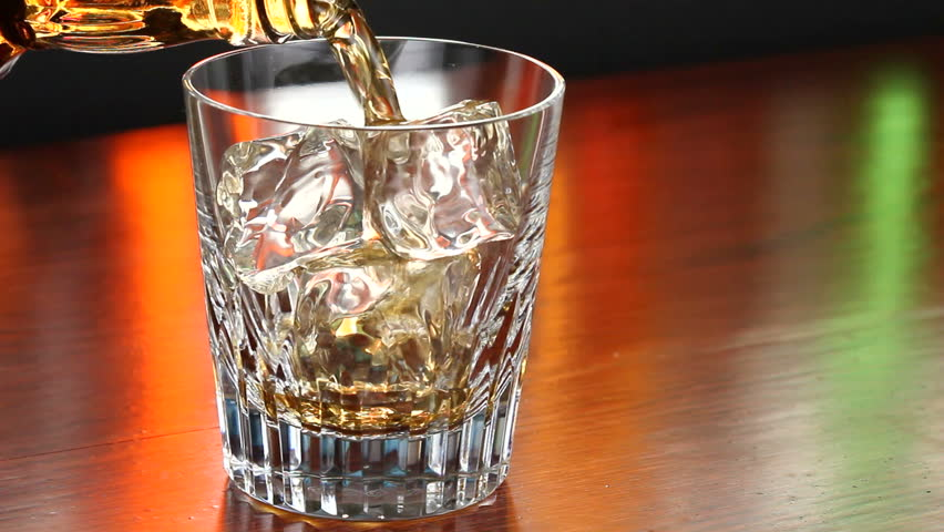 Pouring a scotch whiskey on the rocks - HD stock video clip
